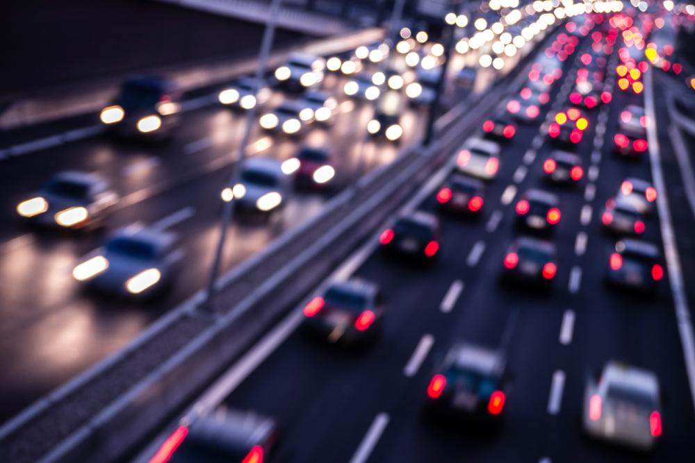 Dálnice za tmy s řadami jedoucích automobilů