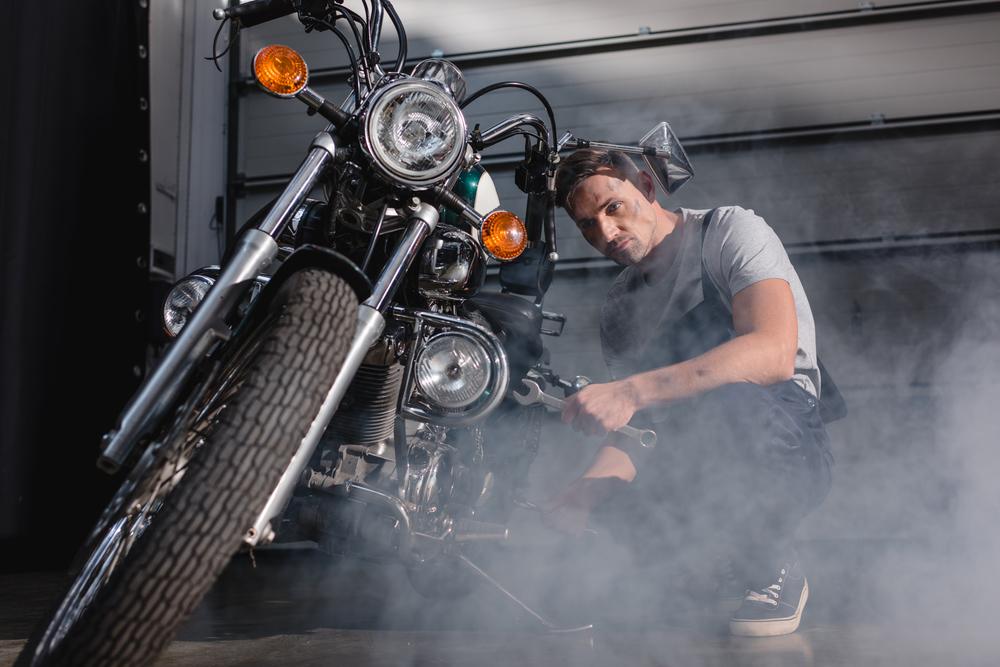 Mechanik opravující motorku v garáži