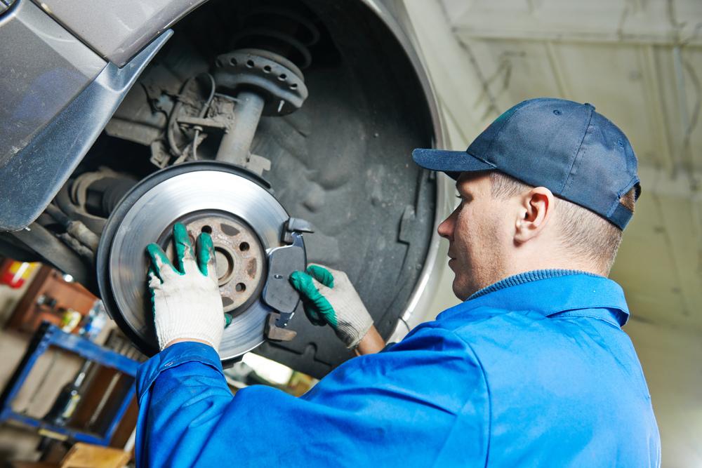 Mechanik opravuje brzdy u automobilu