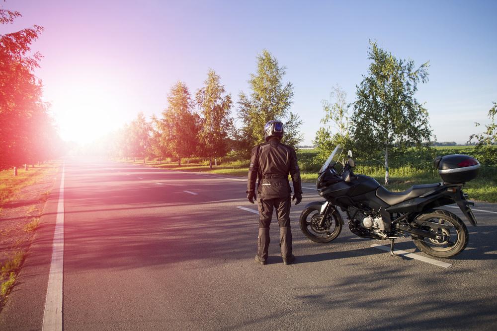 Muž v moto oblečení s motorkou