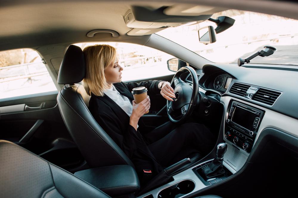 Žena s kávou v ruce za volantem
