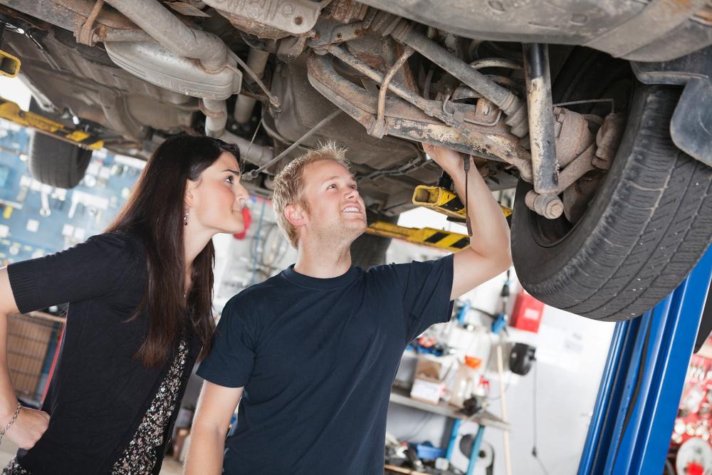 Muž se ženou prohlíží zespodu nápravu auta