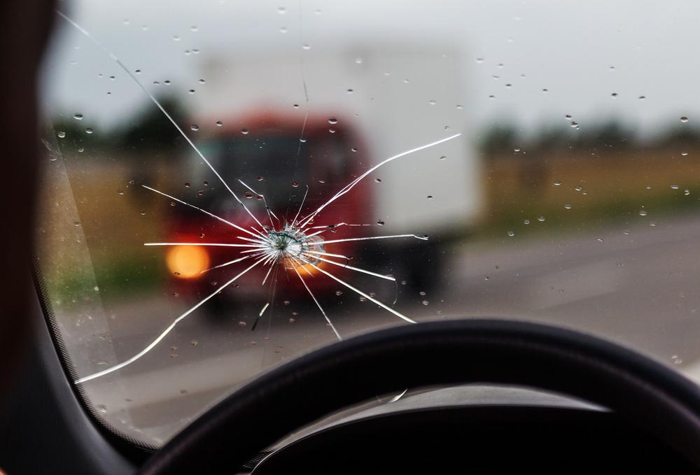 Přední sklo auta s prasklinou z pohledu řidiče