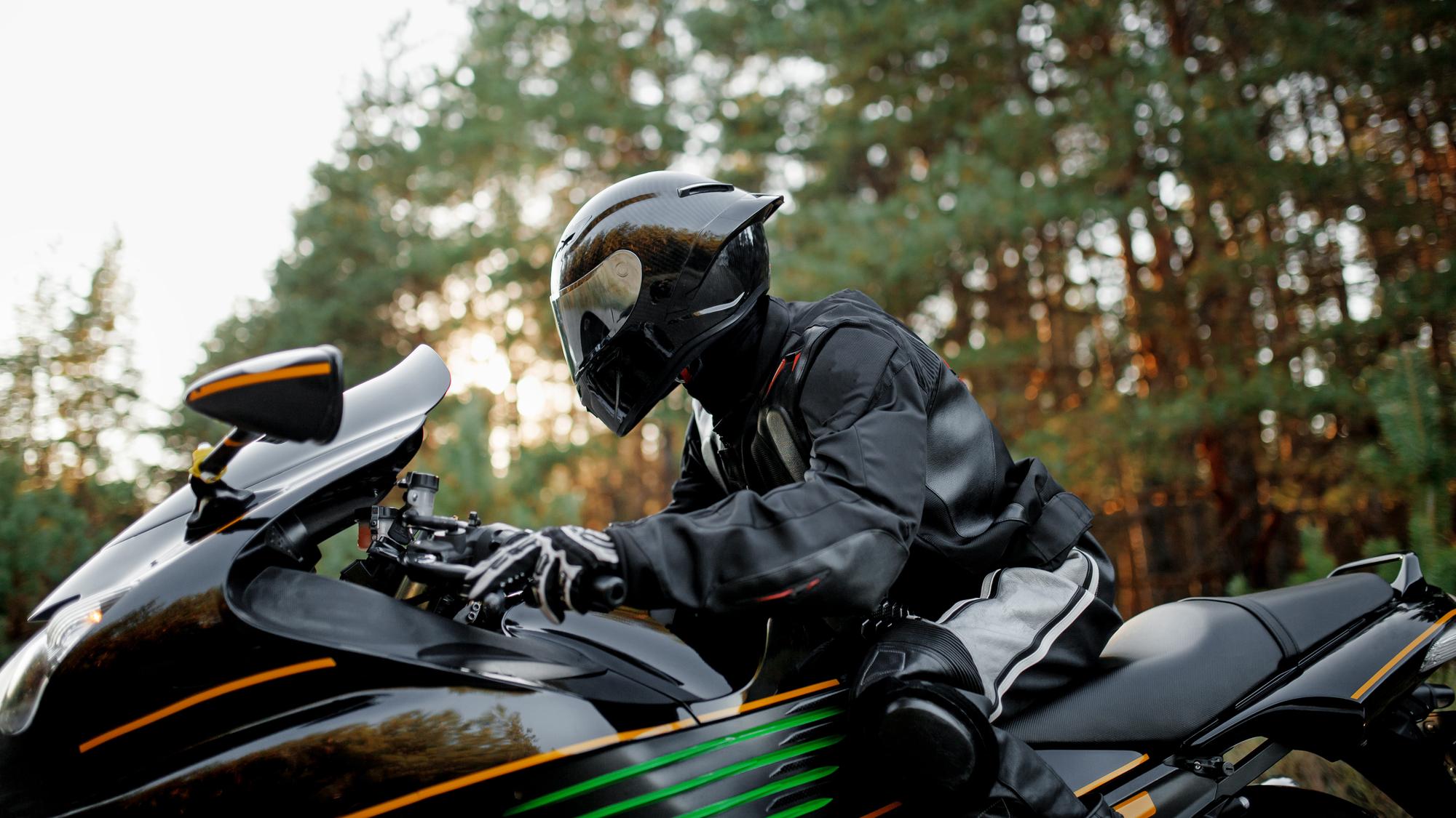 Motorkář na motorce s helmou a kvalitní bundou