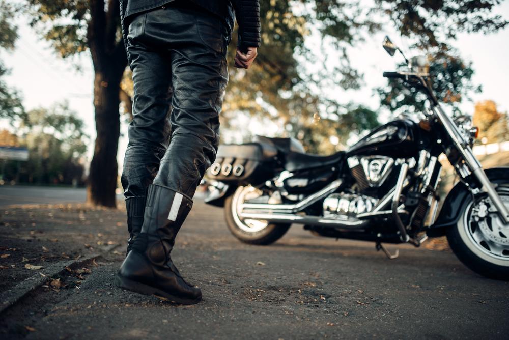 Černé motorkářské boty, kalhoty a motorka v pozadí