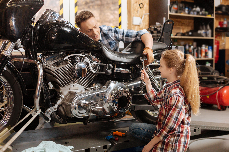 Muž s dcerou opravují motorku v domácí dílně