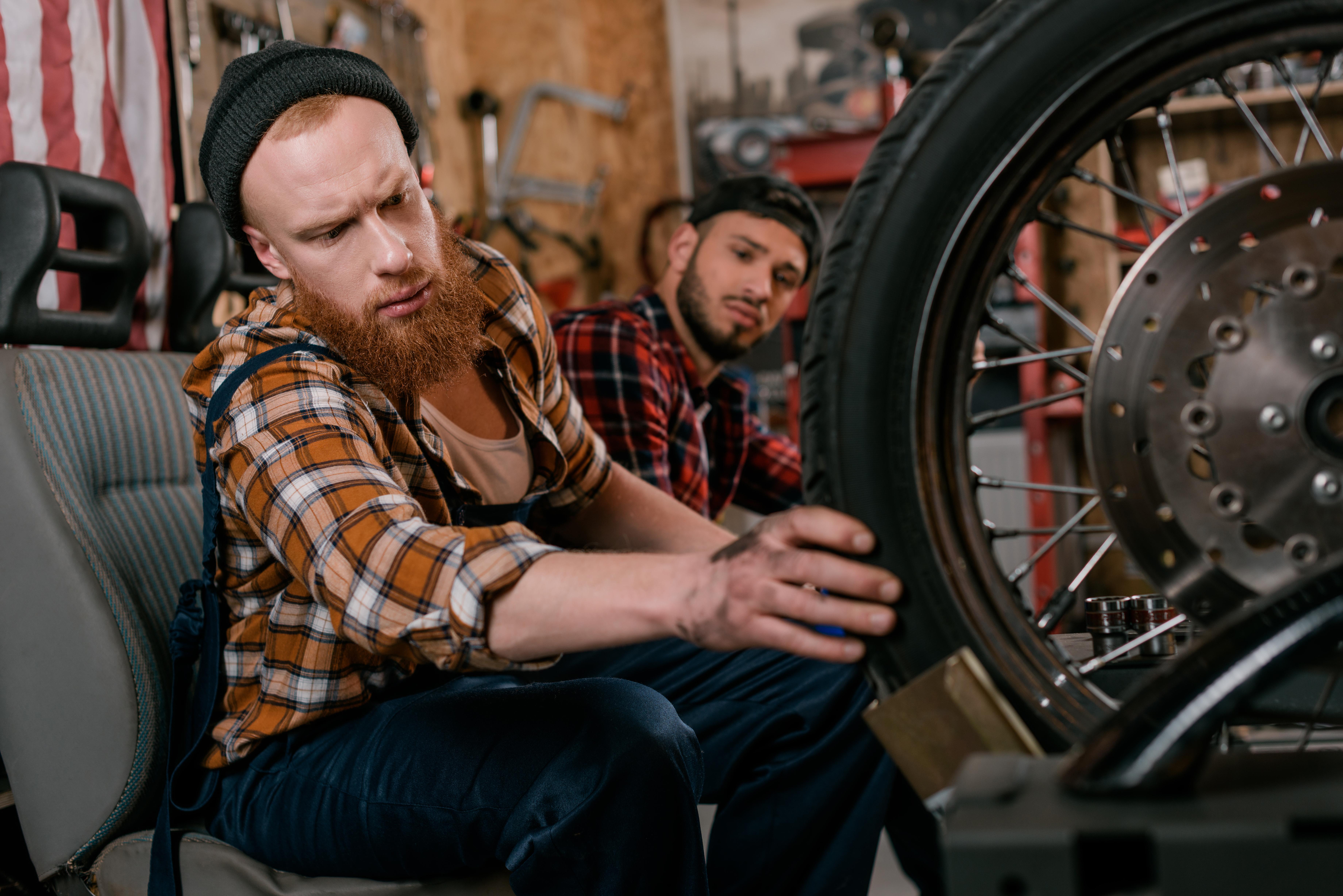 Mladí muži si prohlíží pneumatiku na motorce