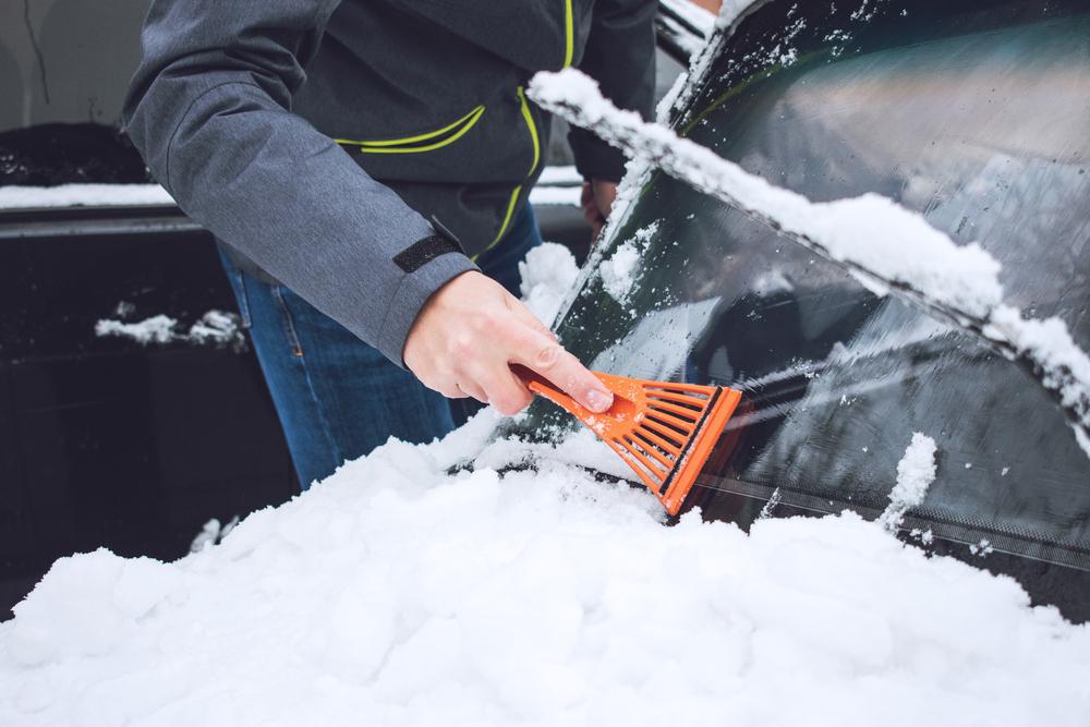 Muž seškrabuje sníh a led ze skla auta