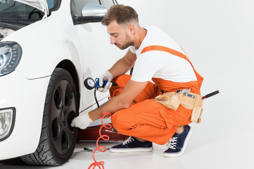 Automechanik měří tlak v pneumatikách
