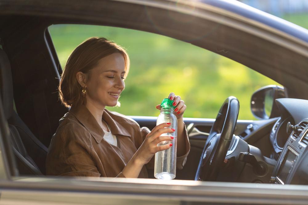 Řidička drží láhev vody
