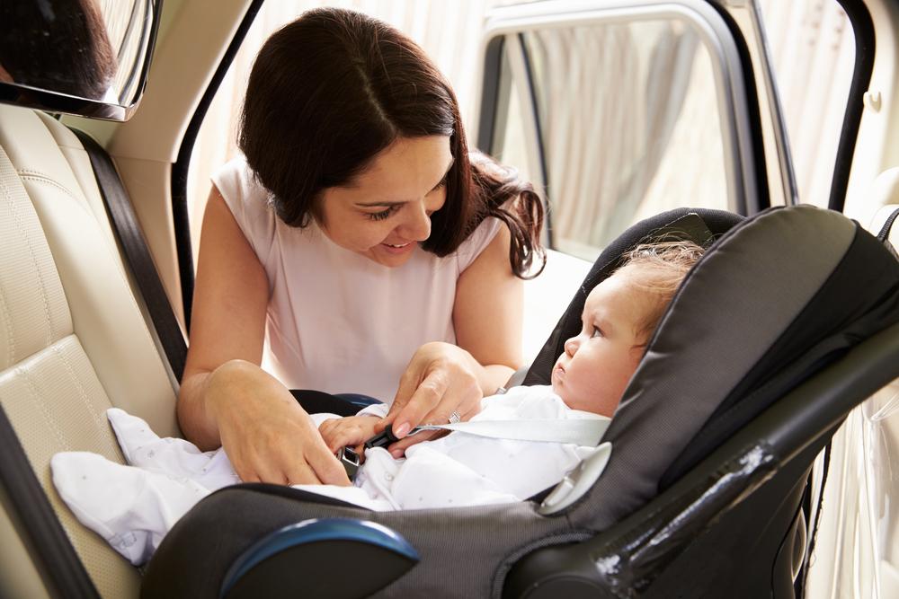 žena upíná dítě v sedačce